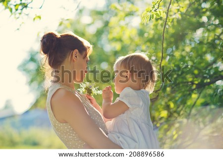 A happy family in the green garden in a sunny spring day: a beautiful young slender mother holding her little laughing daughter in her arms