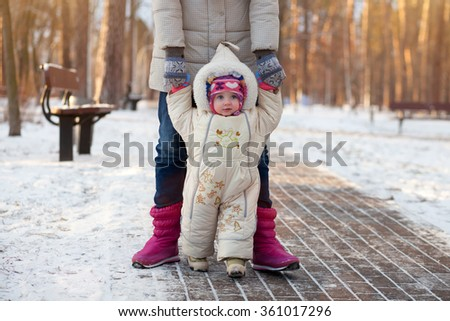 A happy family. Mother teaches a child to walk in winter park. - stock photo