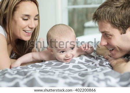 A happy family of father, mother and baby playing in bed