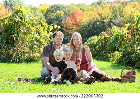 a happy family of four attractive caucasian people is sitting in an apple orchard in the Autumn forest, eating a fresh fruit picnic - stock photo