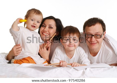 A happy family of four people lying on the bed on a white background
