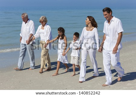 A happy family of grandparents, mother, father and two children, son and daughter, walking holding hands and having fun in the sand of a sunny beach - stock photo