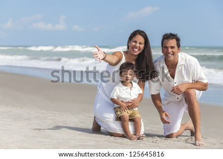 A happy family of mother, father and boy child son, playing and having fun in the sand of a sunny beach.