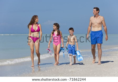 A happy family of mother, father and two children, son and daughter, in swimming costumes having fun in the sea on a sunny beach - stock photo