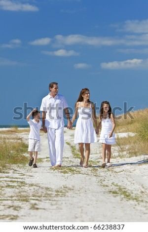 A happy family of mother, father and two children, son and daughter, walking holding hands and having fun in the sand of a sunny beach - stock photo
