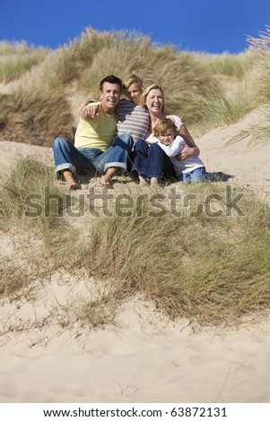 A happy family of mother, father and two sons, sitting and having fun in the sand dunes of a sunny beach