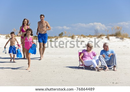 A happy family of mother, father, two children, son and daughter, running having fun on a sunny beach while the grandparents sit looking on and laughing. - stock photo