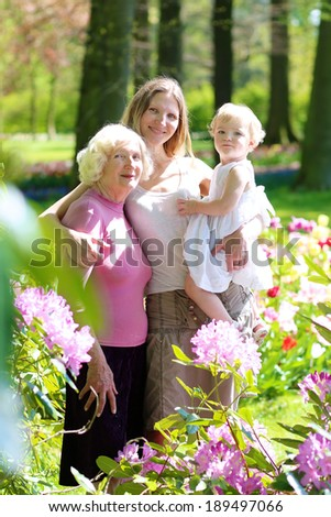 A happy family of three generations, mother, daughter, grandmother and little toddler granddaughter, are standing together in beautiful floral park on a sunny day - stock photo