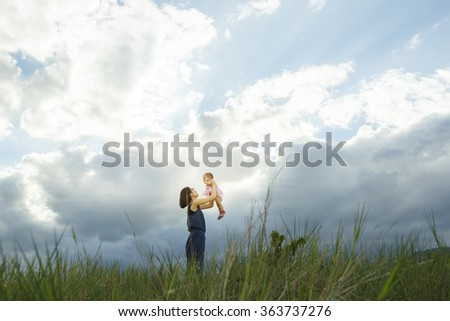 a happy family of two people, mother and baby in front of a sunsetting sky, with copy space or text - Vibrant color effect - stock photo