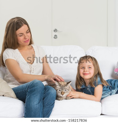 A happy family of two with a cat sitting on sofa and having fun - stock photo