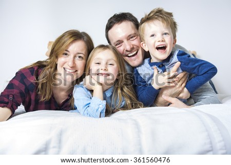 A happy family on white bed in the bedroom - stock photo