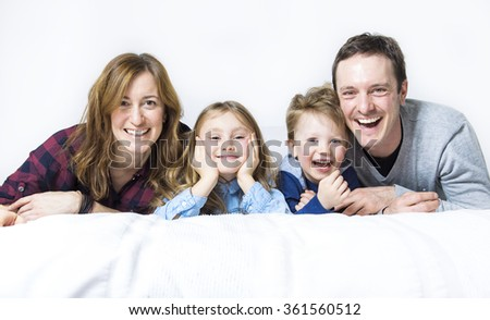 A happy family on white bed in the bedroom