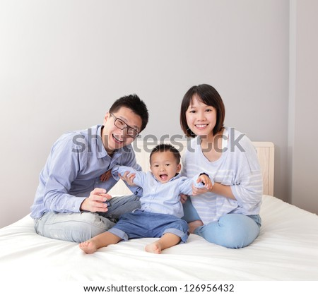 A happy family play on white bed in the bedroom with gray wall for copy space, asian people - stock photo