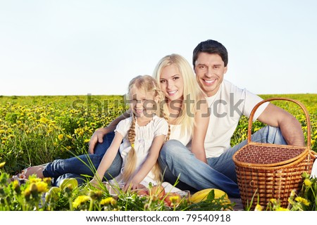 A happy family with a child at a picnic in a field - stock photo