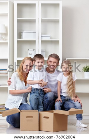A happy family with kids and boxes indoors - stock photo