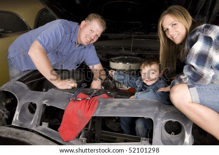 a happy family working together on a car engine with smiles on their faces.