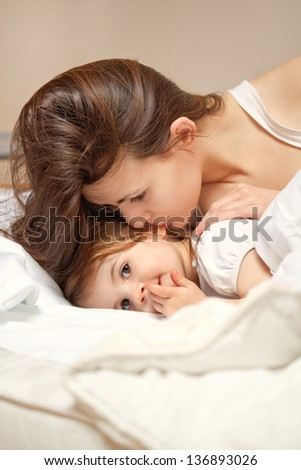 A happy family.  Young Woman and litle girl  in bed