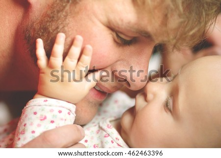 A happy father is playing with his newborn baby daughter, lovingly touching noses while she puts her hand on his cheek.  Shallow depth of field.
