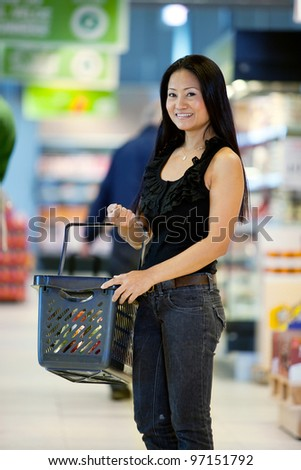 A happy female asian woman with grocery basket in supermarket