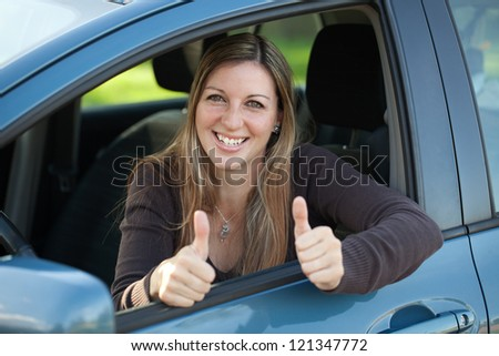 A happy female driver leaning out of the window and showing both thumbs up - stock photo