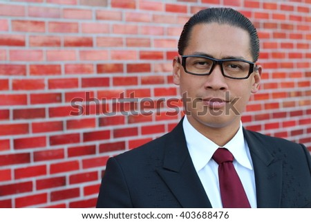 A happy Filipino professional with a confident look (isolated on a red brick wall) - stock photo