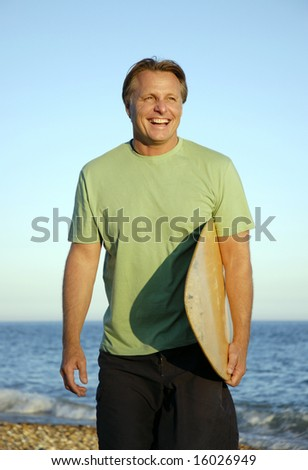 A happy forties man having fun on the beach with his surfboard/skim-board.