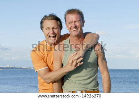 A happy gay couple enjoying a summer`s day on the beach together. - stock photo