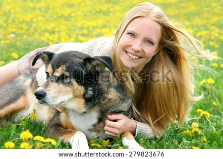 A happy girl is laying in the grass in a dandelion flower meadow, playing with her rescued German Shepherd Mix Dog. - stock photo