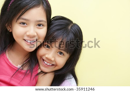 A happy girl posing with her little sister - stock photo