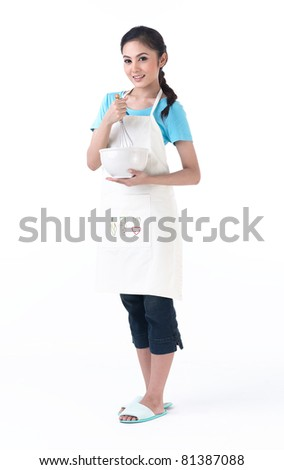 A happy housewife holding a bowl and stirring eggs