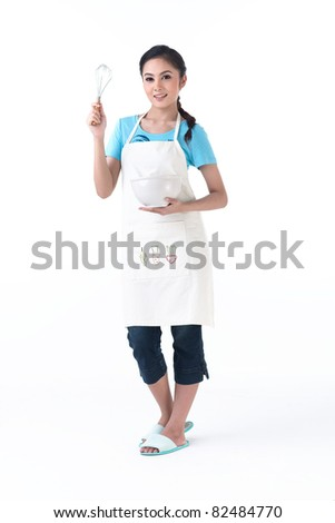 A happy housewife holding a bowl and whisk