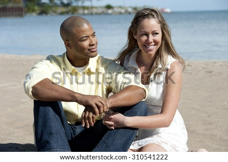 A happy interracial couple sitting at the beach on a sunny day.