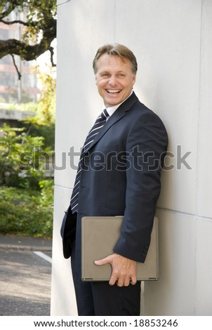 A happy laughing businessman is standing against a wall and holding his laptop computer under his arm