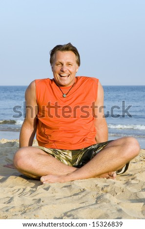 A happy laughing forties man enjoying himself on the beach.