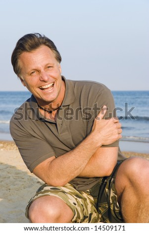A happy laughing forties man is enjoying himself on a beautiful beach.