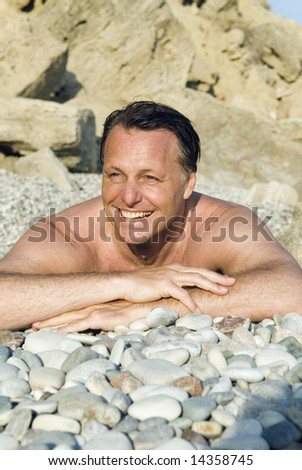 A happy laughing forties man laying on a stony beach in Cyprus.