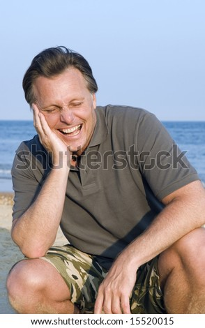 A happy laughing forties man relaxing on the beach.