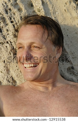 A happy laughing 44 year old man on beach.