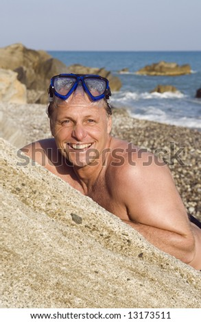 A happy laughing 44 year old man wearing a diving mask is leaning on boulder. - stock photo
