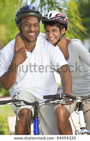 A happy laughing young African American couple with big smiles riding their bicycles outside