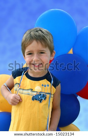 a happy little boy holds a bundle of balloons - stock photo