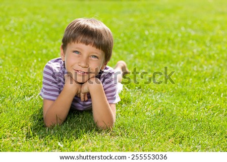 A happy little boy is lying on the green grass - stock photo
