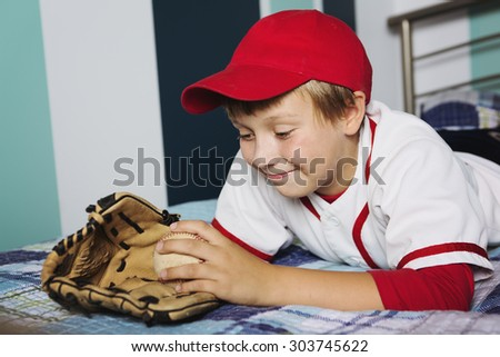 A Happy little boy playing baseball in his bedroom - stock photo