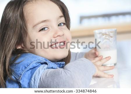 A Happy little child drinking milk on a kitchen - stock photo