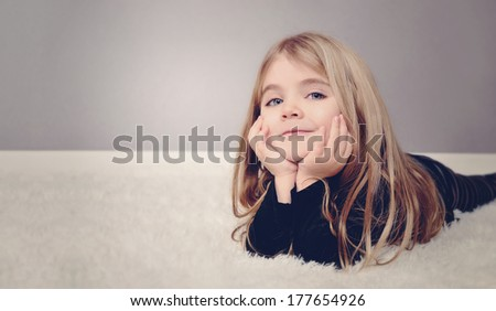 A happy little girl is laying on the white floor with copyspace area for a text message. Use it for a home or family concept. - stock photo