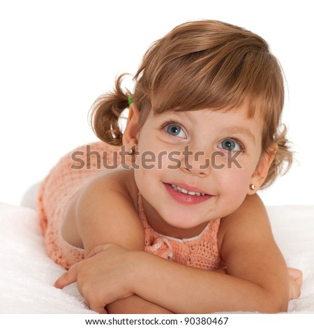 A happy little girl is lying on the bedspread; isolated on the white background - stock photo