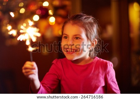A happy little girl playing with a sparkler - stock photo