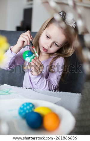 A happy little kid coloring easter eggs. Cozy home atmosphere. Easter - stock photo
