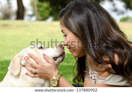a happy looking woman nose to nose with her pet dog. - stock photo