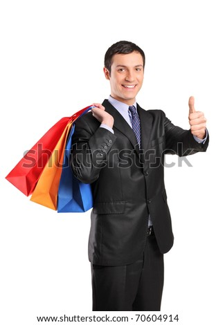 A happy male holding shopping bags and giving thumb up isolated on white background - stock photo